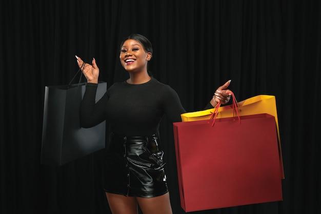 Junge afroamerikanerfrau, die mit bunten packungen auf schwarz einkauft