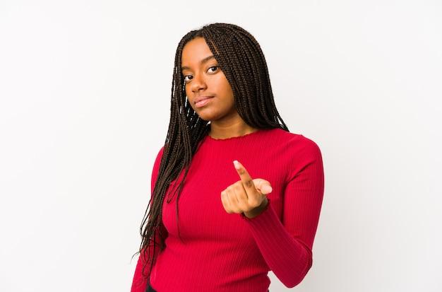 Junge afroamerikanerfrau, die mit dem finger auf sie zeigt, als ob die einladung näher kommt.