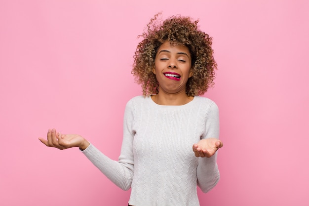 Junge afroamerikanerfrau, die mit einem dummen, verrückten, verwirrten, verwirrten ausdruck die achseln zuckt, sich genervt und ahnungslos gegen rosa wand fühlt