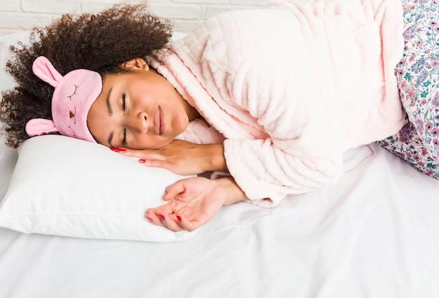 Junge afroamerikanerfrau, die mit einem kissen auf dem bett schläft