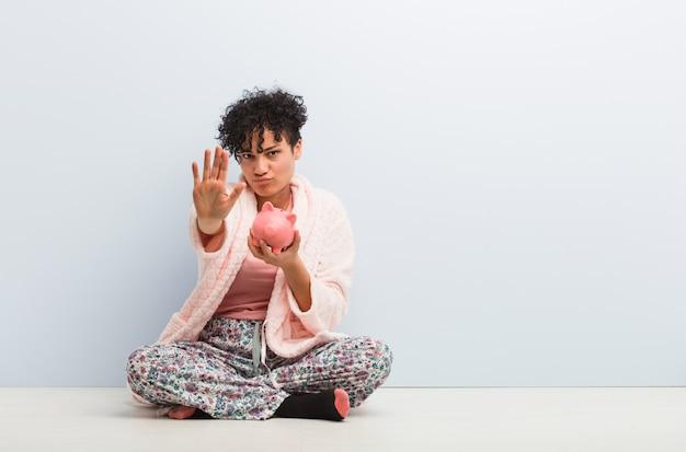 Junge afroamerikanerfrau, die mit einem sparschwein steht mit der ausgestreckten hand zeigt stoppschild sitzt