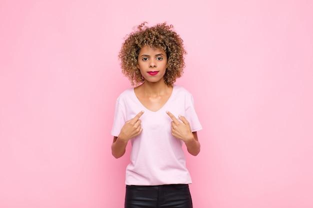 Junge afroamerikanerfrau, die mit einem verwirrten und fragenden blick auf sich selbst zeigt, schockiert und überrascht, gegen rosa wand gewählt zu werden