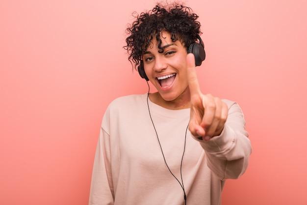 Junge afroamerikanerfrau, die musik zeigt nummer eins mit dem finger hört.