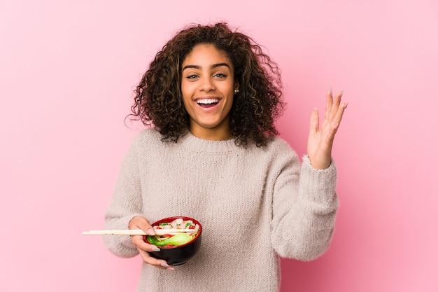 Junge afroamerikanerfrau, die nudeln isst, die eine angenehme überraschung erhalten, aufgeregt und hände heben.