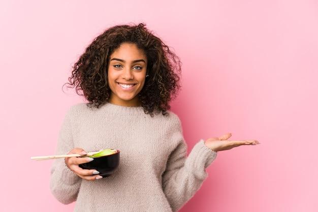 Junge afroamerikanerfrau, die nudeln isst, die einen kopienraum auf einer handfläche zeigen und eine andere hand auf taille halten.