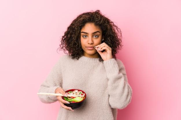 Junge afroamerikanerfrau, die nudeln mit den fingern auf den lippen isst, die ein geheimnis halten.