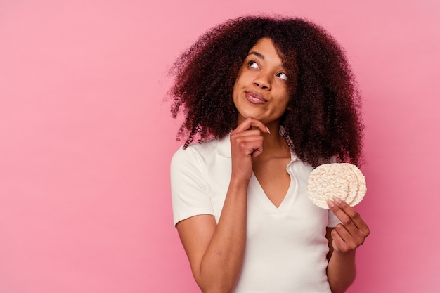 Junge afroamerikanerfrau, die reiskuchen isst lokalisiert auf rosa hintergrund, der seitwärts mit zweifelhaftem und skeptischem ausdruck schaut.