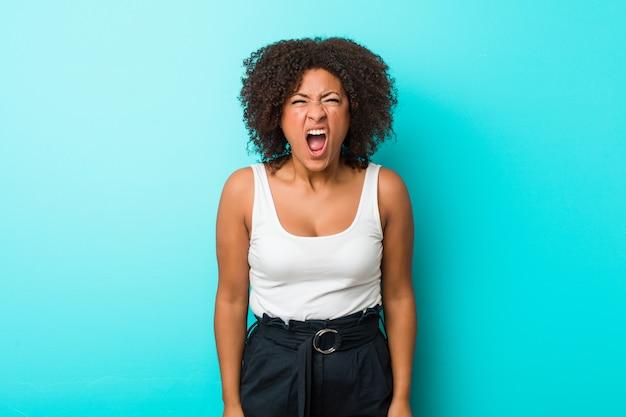 Junge afroamerikanerfrau, die sehr verärgert und aggressiv schreit.