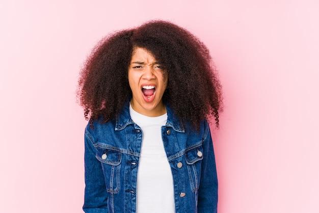 Junge afroamerikanerfrau, die sehr wütend und aggressiv schreit.