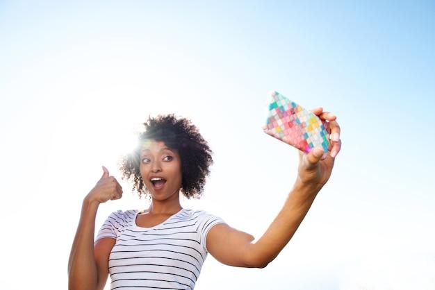 Junge afroamerikanerfrau, die selfie mit handy nimmt
