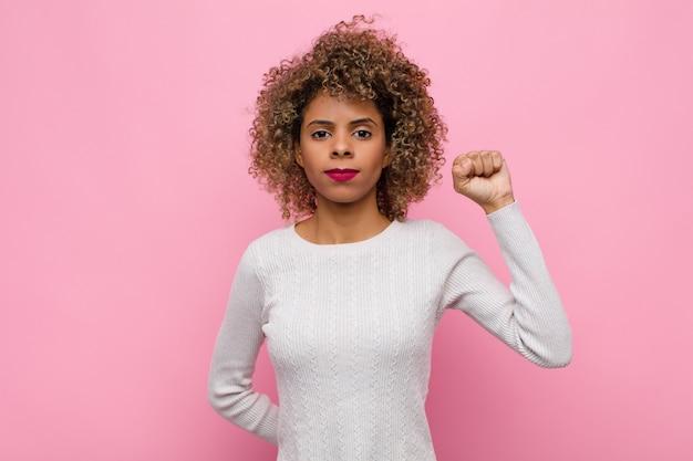 Junge afroamerikanerfrau, die sich ernst, stark und rebellisch fühlt, faust erhebt, protestiert oder für revolution über rosa wand kämpft