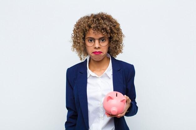 Junge afroamerikanerfrau, die traurig und weinerlich mit einem unglücklichen blick fühlt und mit einer negativen und frustrierten haltung mit einem sparschwein weint