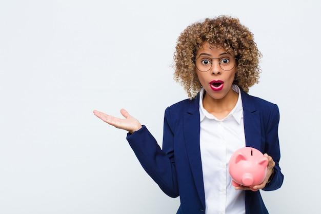 Junge afroamerikanerfrau, die überrascht und schockiert schaut, mit gesenktem kiefer, der einen gegenstand mit einer offenen hand auf der seite mit einem sparschwein hält