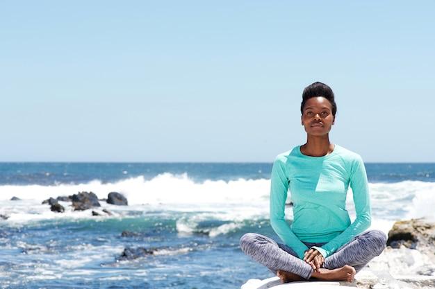 Junge afroamerikanerfrau, die yoga am strand tut