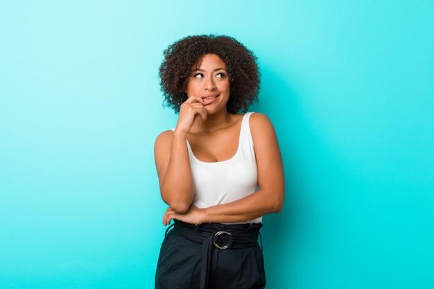 Junge afroamerikanerfrau entspannte sich das denken an etwas, das eine kopie betrachtet.