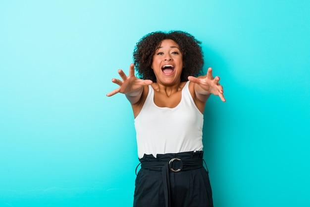 Junge afroamerikanerfrau fühlt sich überzeugt, der kamera eine umarmung gebend.
