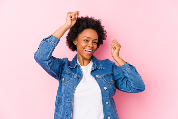 Junge afroamerikanerfrau gegen einen rosa hintergrund, der einen besonderen tag feiert, springt und arme mit energie hebt.