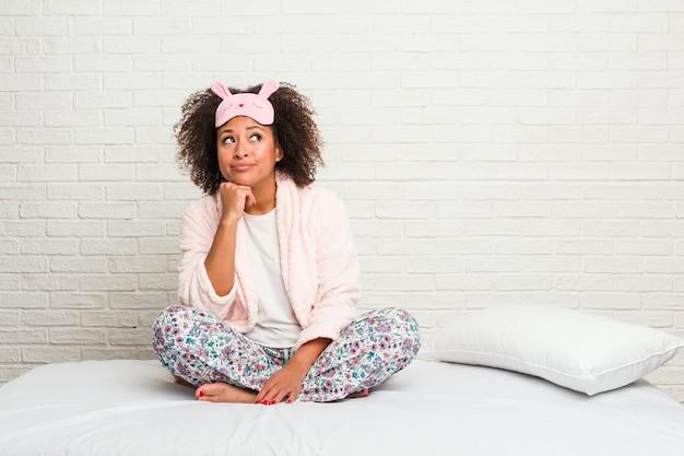 Junge afroamerikanerfrau im bett, die pijama trägt, das seitwärts mit zweifelhaftem und skeptischem ausdruck schaut.