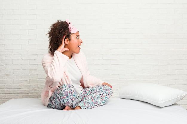 Junge afroamerikanerfrau im bett, die pijama trägt, der versucht, einen klatsch zu hören.