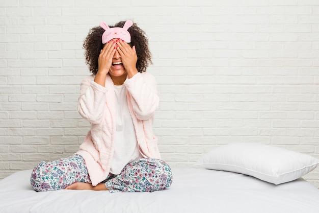 Junge afroamerikanerfrau im tragenden pijama des betts bedeckt augen mit den händen, lächelt auf eine überraschung breit warten.