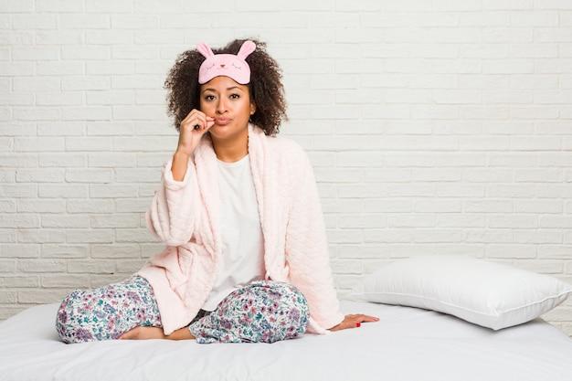 Junge afroamerikanerfrau im tragenden pijama des betts mit den fingern auf den lippen, die ein geheimnis halten.