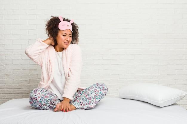 Junge afroamerikanerfrau im tragenden pijama leidenden nackenschmerzen des betts wegen des sitzenden lebensstils.