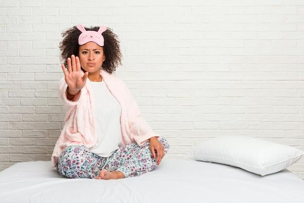 Junge afroamerikanerfrau im tragenden pyjama des betts