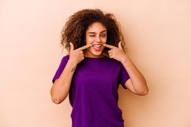 Junge afroamerikanerfrau lokalisiert auf beige wandlächeln, finger auf mund zeigend