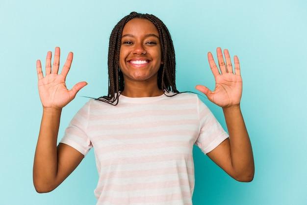 Junge afroamerikanerfrau lokalisiert auf blauem hintergrund, der nummer zehn mit den händen zeigt.