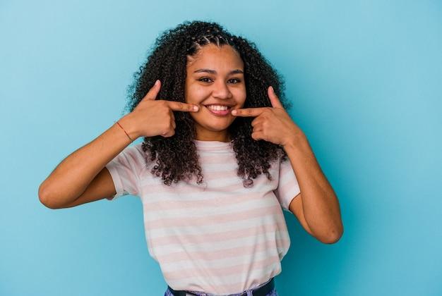 Junge afroamerikanerfrau lokalisiert auf blauem hintergrund lächelt und zeigt finger auf mund.