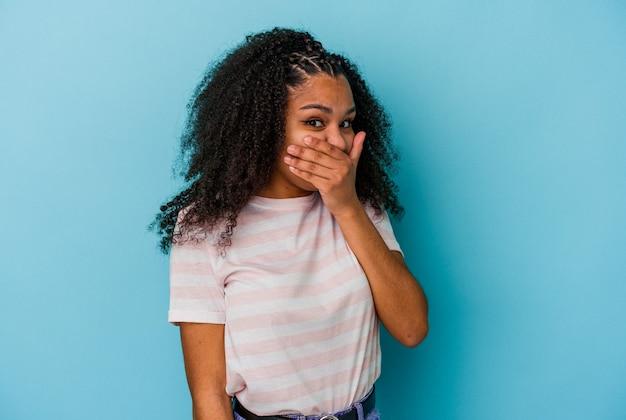 Junge afroamerikanerfrau lokalisiert auf blauer wand ängstlich und ängstlich