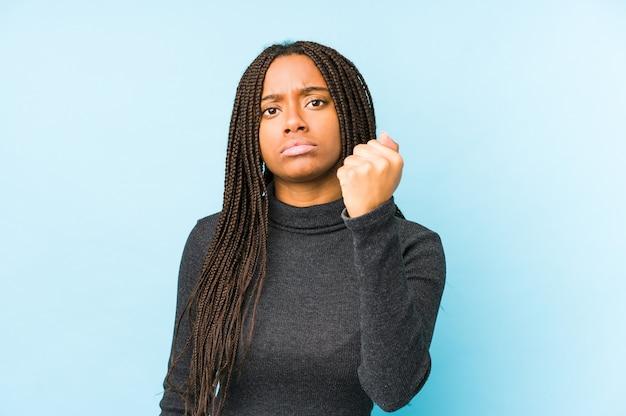 Junge afroamerikanerfrau lokalisiert auf blauer wand, die faust, aggressiven gesichtsausdruck zeigt.