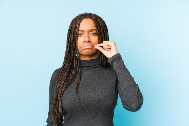 Junge afroamerikanerfrau lokalisiert auf blauer wand mit den fingern auf den lippen, die ein geheimnis halten.