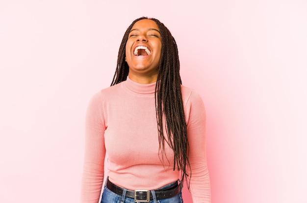 Junge afroamerikanerfrau lokalisiert auf einer rosa wand entspannt und glücklich lachend, hals gestreckt, der zähne zeigt.