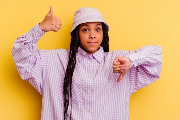 Junge afroamerikanerfrau lokalisiert auf gelbem hintergrund, der daumen oben und daumen unten zeigt, schwieriges auswahlkonzept