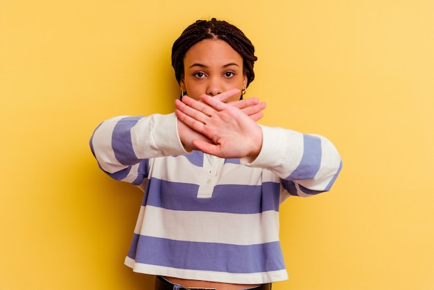 Junge afroamerikanerfrau lokalisiert auf gelbem hintergrund, der eine verweigerungsgeste tut