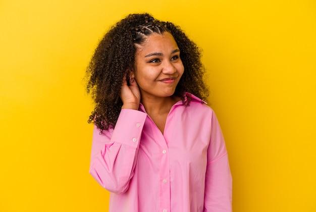 Junge afroamerikanerfrau lokalisiert auf gelbem hintergrund, der ohren mit den händen bedeckt.