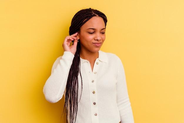 Junge afroamerikanerfrau lokalisiert auf gelbem hintergrund, der ohren mit händen bedeckt.