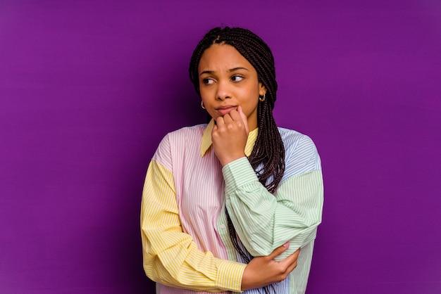 Junge afroamerikanerfrau lokalisiert auf gelbem hintergrund verwirrt, fühlt sich zweifelhaft und unsicher.