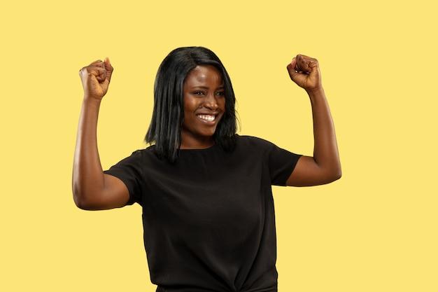 Junge afroamerikanerfrau lokalisiert auf gelbem studiohintergrund, gesichtsausdruck. schönes weibliches halblanges porträt. konzept menschlicher emotionen, gesichtsausdruck. verrückt glücklich, feiern.
