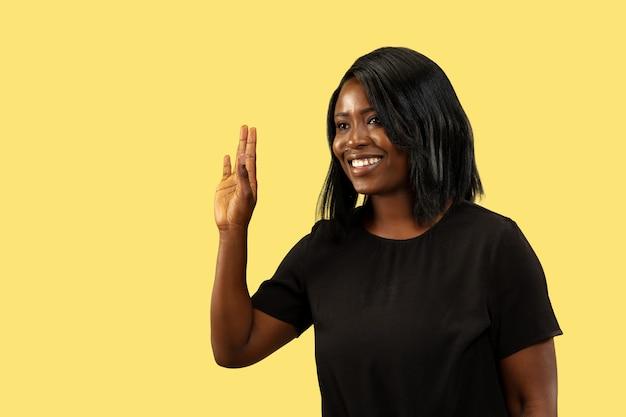 Junge afroamerikanerfrau lokalisiert auf gelbem studiohintergrund, gesichtsausdruck. schönes weibliches halblanges porträt. konzept menschlicher emotionen, gesichtsausdruck. zeige das zeichen des tschüss.