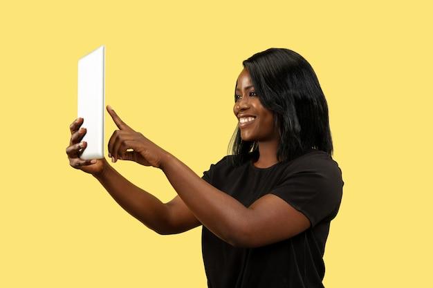 Junge afroamerikanerfrau lokalisiert auf gelbem studiohintergrund, gesichtsausdruck. schönes weibliches porträt. konzept menschlicher emotionen, gesichtsausdruck. tablet für selfie oder vlog verwenden.