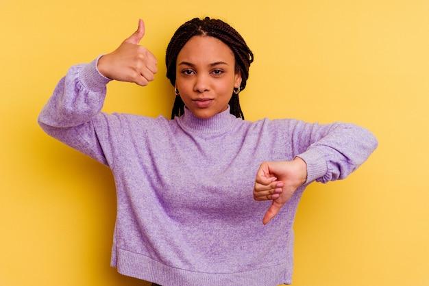 Junge afroamerikanerfrau lokalisiert auf gelber wand, die daumen oben und daumen unten zeigt