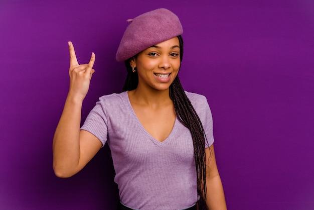 Junge afroamerikanerfrau lokalisiert auf gelber wand, die felsengeste mit den fingern zeigt