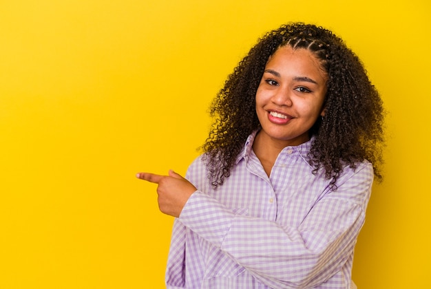 Junge afroamerikanerfrau lokalisiert auf gelber wand, die lächelt und beiseite zeigt und etwas an der leeren stelle zeigt.