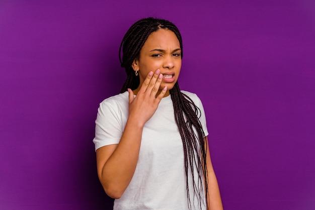 Junge afroamerikanerfrau lokalisiert auf gelber wand, die starken zahnschmerz, backenzahnschmerz hat.