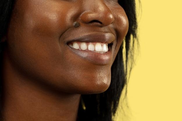 Junge afroamerikanerfrau lokalisiert auf gelber wand, gesichtsausdruck. schönes weibliches lächeln schließen nahporträt. konzept menschlicher emotionen, gesichtsausdruck.