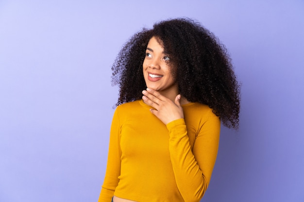 Junge afroamerikanerfrau lokalisiert auf lila, die beim lächeln nach oben schaut