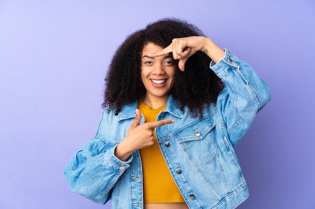 Junge afroamerikanerfrau lokalisiert auf lila fokussierendem gesicht. rahmensymbol