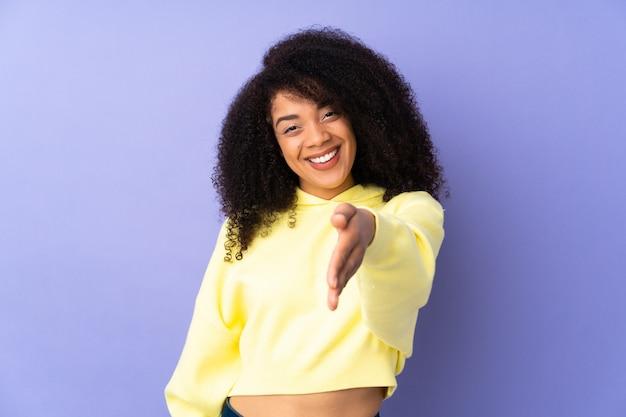 Junge afroamerikanerfrau lokalisiert auf lila händeschütteln für das schließen eines guten geschäfts